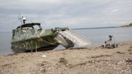 Led by the Naval Surface Warfare Center Indian Head Explosive Ordnance Disposal Technology Division, this simulated mission involves deploying Explosive Ordnance Disposal Unmanned Ground Vehicle (UGV) assets from a converted autonomous Advanced Composite